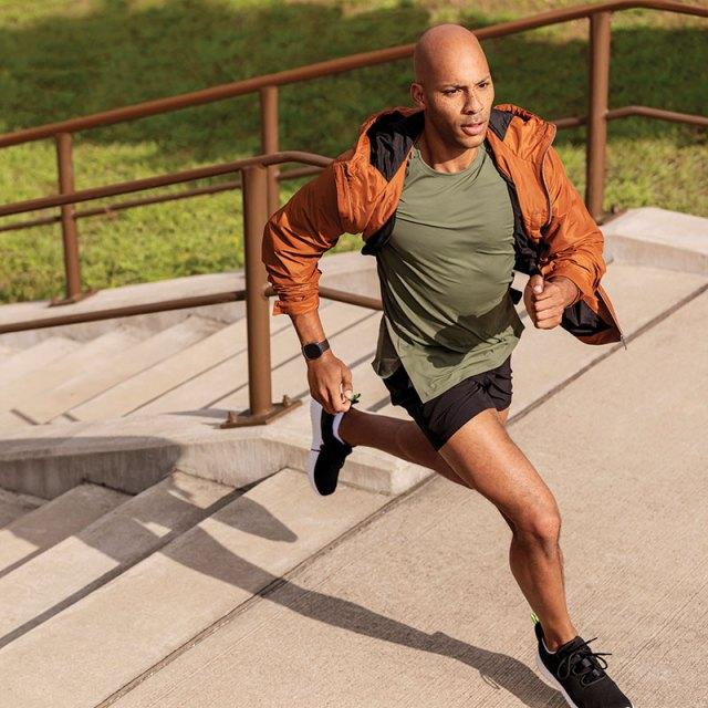 Man running up stairs while wearing fitbit sense