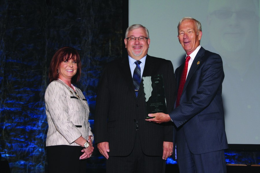 Brad Roos, center, receives the James. D. Donovan Individual Achievement Award from APPA board chair Paula DiFonzo and past chair Gary Stauffer.
