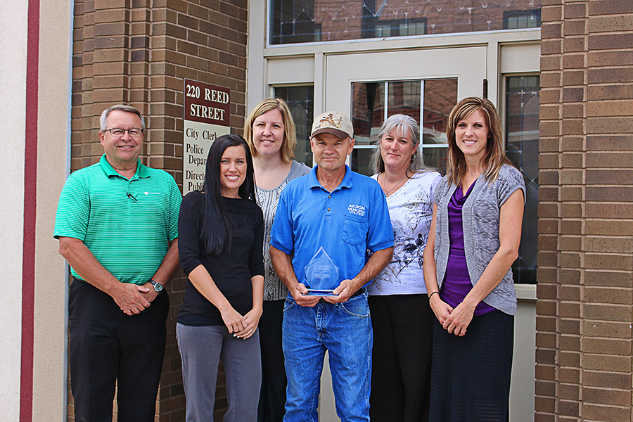 Gary Horton, center, accepts the Distinguished Service Award from Heartland officials and Akron city staff. From left to right: Heartland Customer Relations Manager Steve Moses, Akron TITLE TITLE NAME NAME, Clerk Melea Nielsen, Deputy Clerk Karen Wardrip and Heartland Communications Manager Ann Hyland.