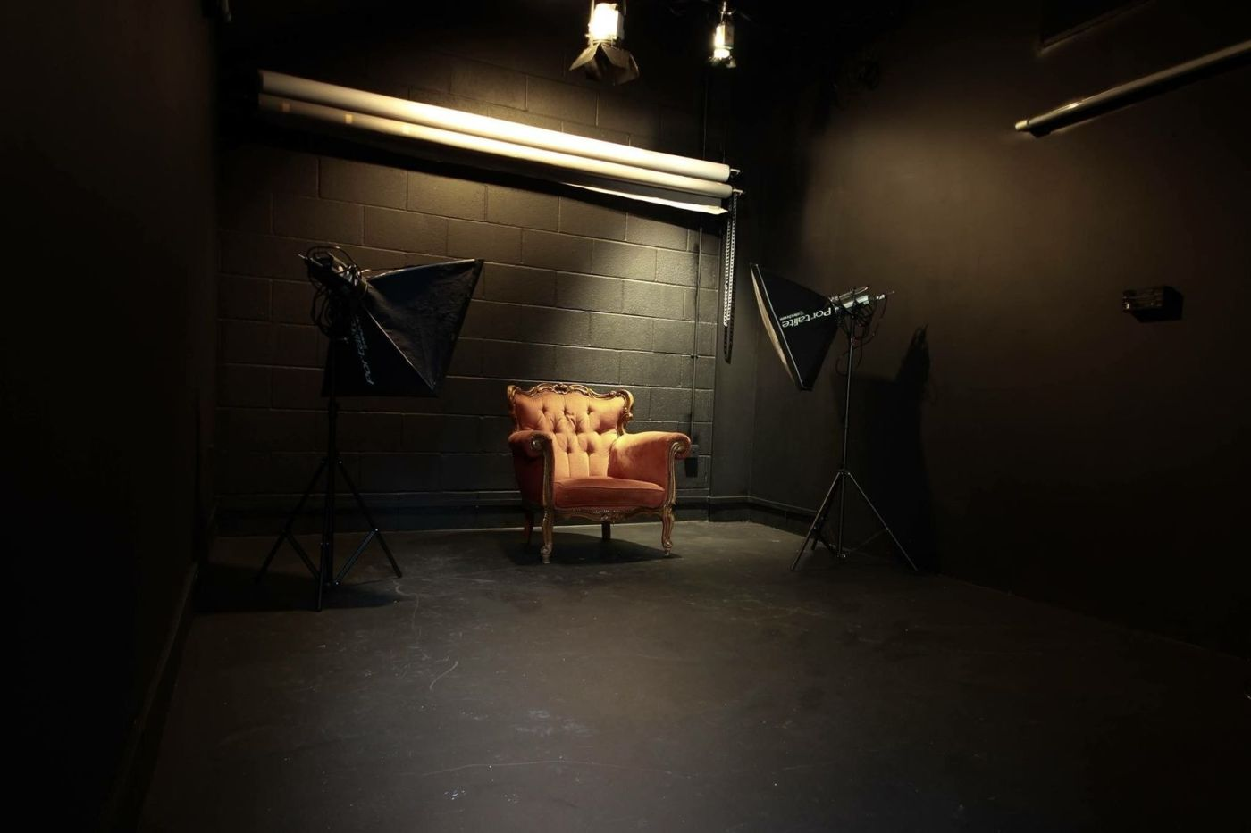 A black studio with one orange chair and two studio lights
