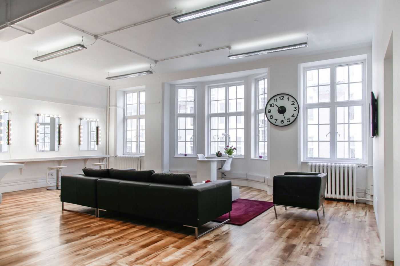 A large studio with two black sofas and large windows.