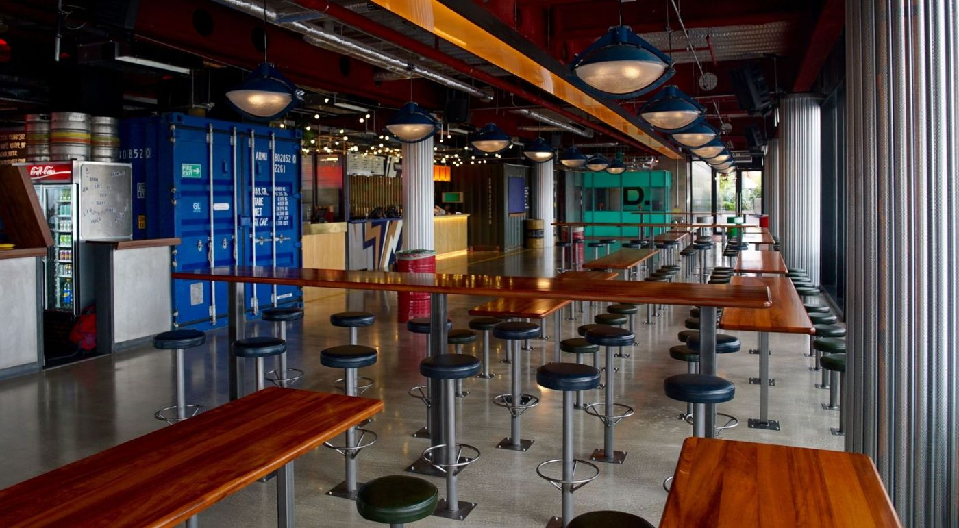 An industrial street food venue in East London. The venue has old shipping containers inside and has plenty of high bar tables and stools.