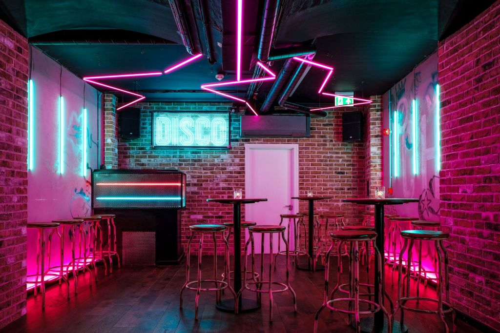 a bar with pink neon tube lighting and brick walls.