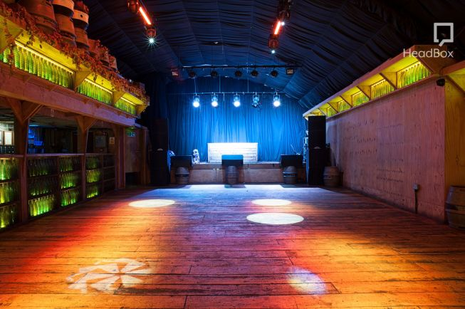 a dark warehouse is lit up with orange and blue lights. There is a bar running along one side of the venue and a stage set up at the back of the room.