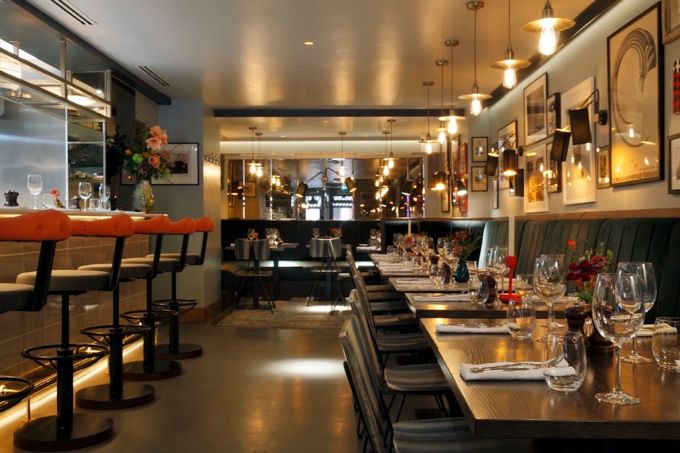 Galley Restaurant in North London. A modern room with a bar along the left wall with tall orange bar stalls places in front. Tables sit along the opposite wall with grey chairs tucked under neath. The right wall is adorned with framed pictures and a mirror reflects the length of the restaurant.