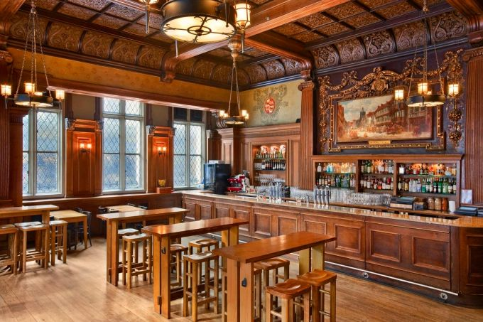 A traditional english pub with oak furniture and panelled walls. There is a large oil painting hanging on the wall behind the bar.
