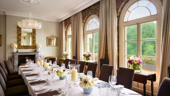 A beautiful private dining with a white table and brown chairs all set up for a dinner. There are yellow flowers arranged along the table as well as wine glasses and cutlery. The big windows look out onto greenery.