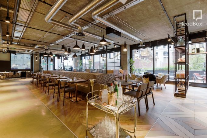 Drake and Morgan restaurant in North London. A bright large Space with exposed ceiling and floor to ceiling windows running the length of the outer walls. Light grey leather benches fact outwards in the centre of the room with tables arranged in from of them. A stocked gold drinks trolly sits in the front centre of the photo.