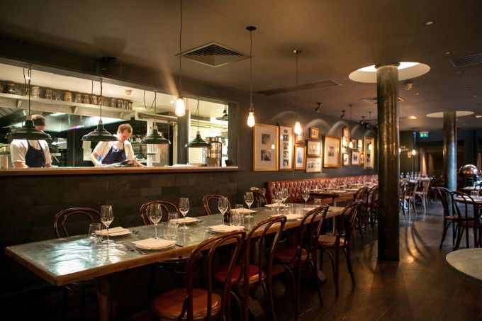 Private dining at Jamie Oliver's Fifteen restaurant in London. A dimly lit restaurant with grey brick walls adorned with frames. Low hanging light bulbs hang over long dining tables set for supper. A window looks into the kitchen where two chefs are working.