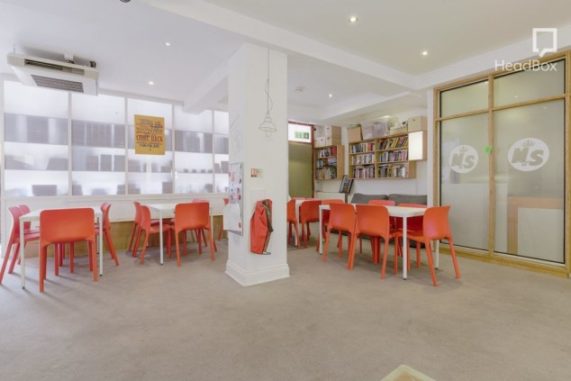 A training room with bookshelves along one wall, several white tables surrounded by orange chairs.