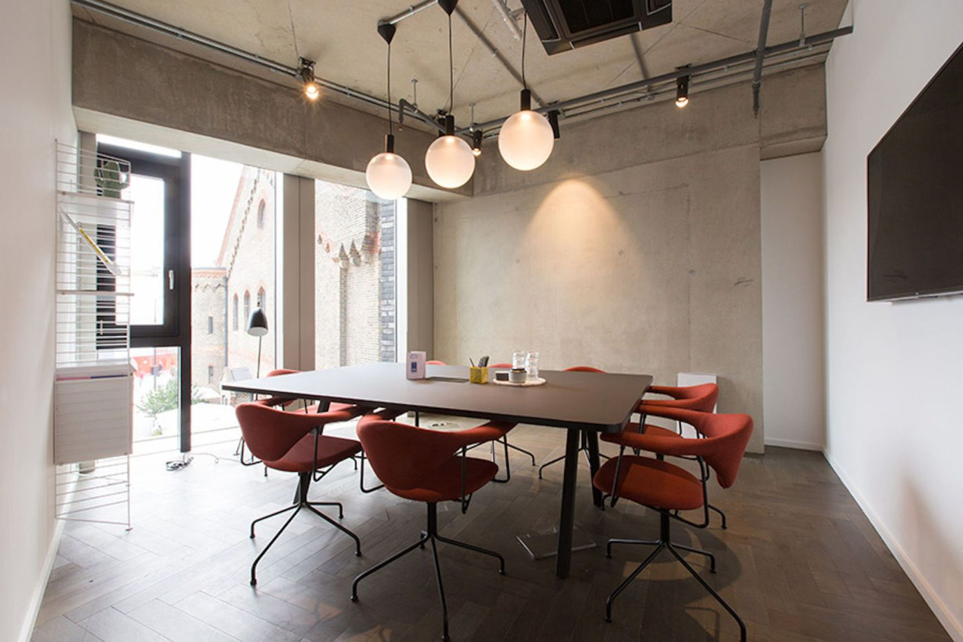 A large meeting room with concrete walls and orange chairs