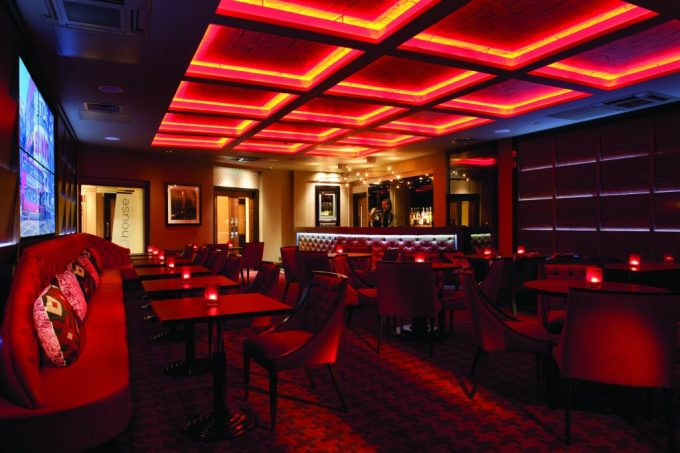 a large restaurant is dimly lit with a red artificial light. There are various small tables and chairs across the floor as well as a red banquet sofa.
