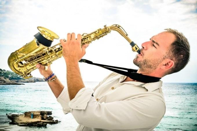 man in white playing saxophone