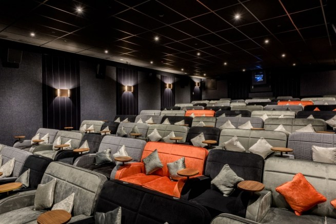 a large cinema shows comfy sofa charis in grey, orange and black which all have crushed velvet pillows on them. The walls to the screening room are black with lights on the sides and spotlights on the ceiling.
