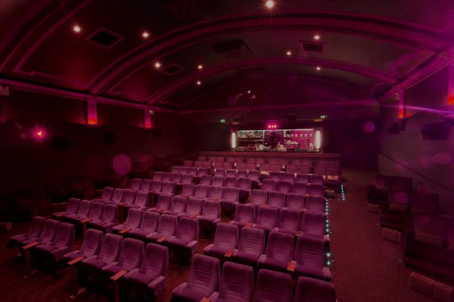 a purple theatre with rows of chairs all facing the same direction