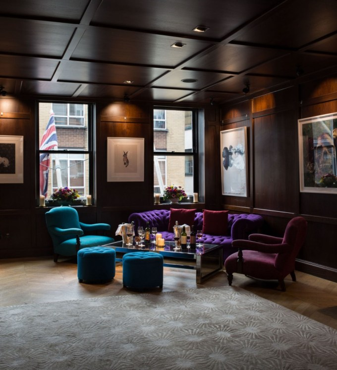 Secluded informal meeting space with blue and purple velvet sofa and chairs surrounding a short coffee table laid with refreshments.