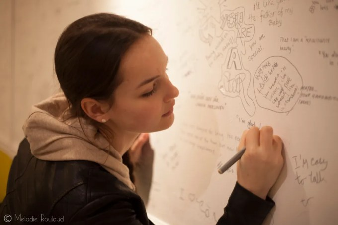 a woman writing on a large whiteboard wall which already has lots of writing and doodles on it.