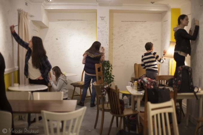 four people writing on the walls of a cafe. There are various chairs and tables in the room.