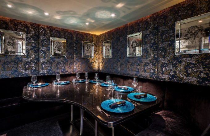 there is a large brown dining table in the centre of a room. On the table are gaudy blue plated with black napkins, silver cutlery and wine glasses. The walls are covered in a dark purple, printed wallpaper and there are square mirrors along the wall.