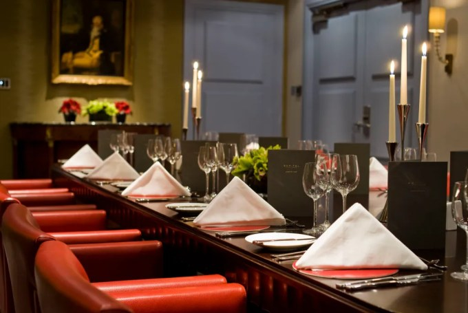 a close up shot of a brown table set up for a meal. There are red leather chairs pushed up against the table.