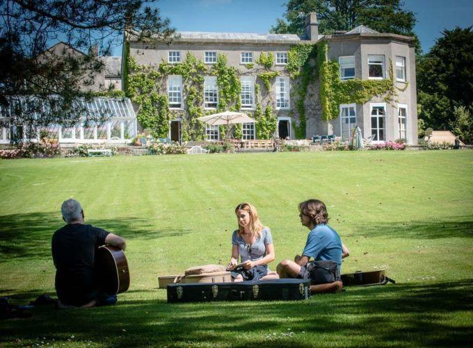 Three people enjoy sun playing guitar
