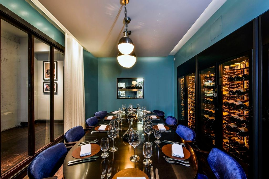 A private dining room which has a long wooden table in the middle that is surrounded by blue velvet chairs. On the right hand side there is a wine rack full of wine.