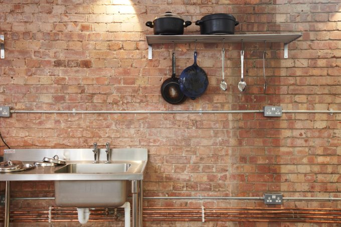 brick wall with pans on shelf