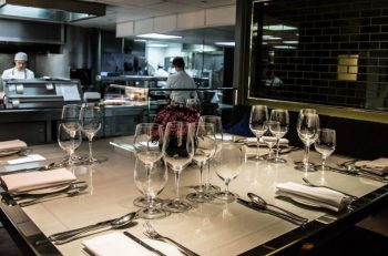 square private dining table laid with cutlery