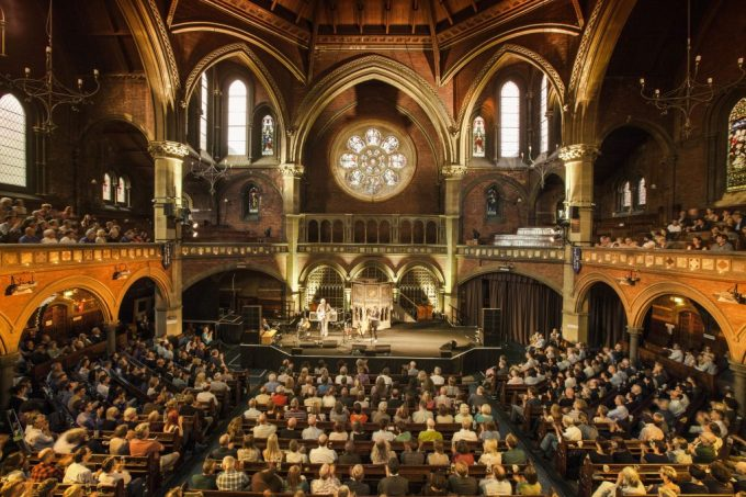 the grand interior of a chapel shows hundreds of people all facing a stage where a band is performing. The balcony levels are also filled with people and the large chapel windows are letting in natural daylight