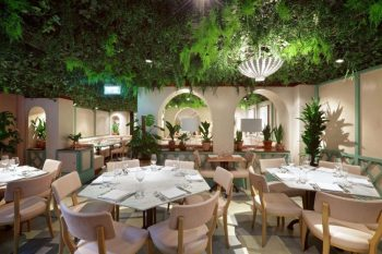 dining room with hexagonal white tables and pink chairs with foliage coming out of the ceiling