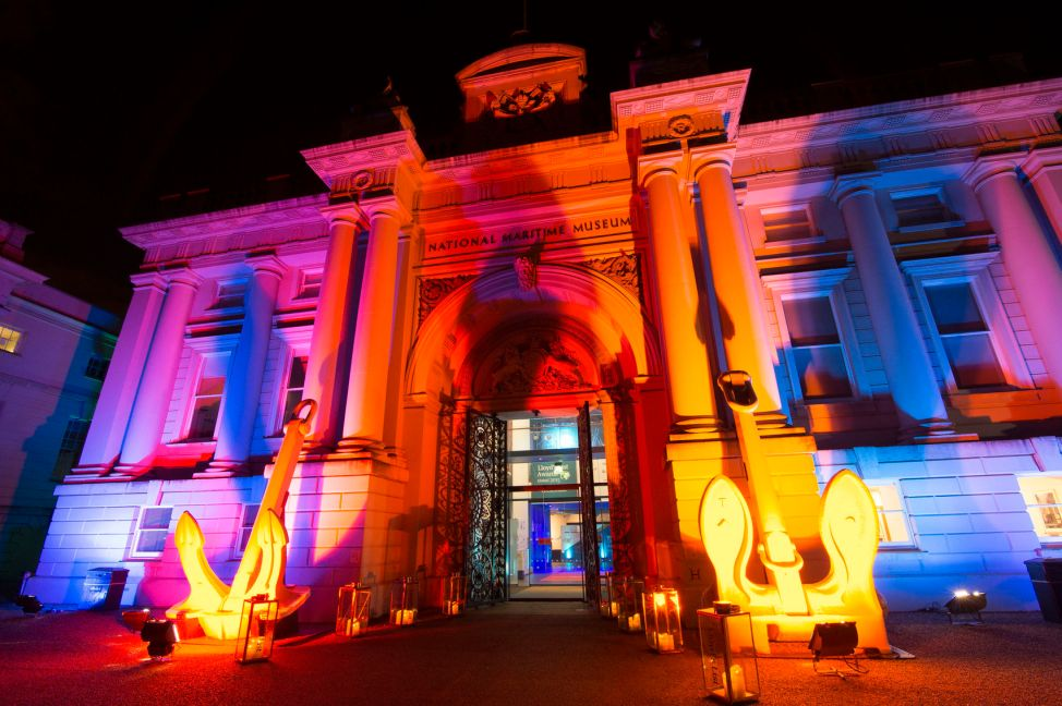 The outside of The National Maritime Museum which has a large, grand doorway and the building is lit up in purple, orange and yellow light.