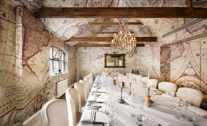 a bright and spacious private dining room has walls that are covered in maps. There is a large chandelier hanging on the ceiling above the table and strong wooden beams bun across the ceiling