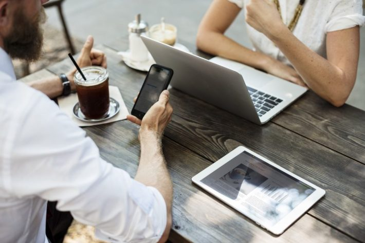 Two people sat at table with macbooks