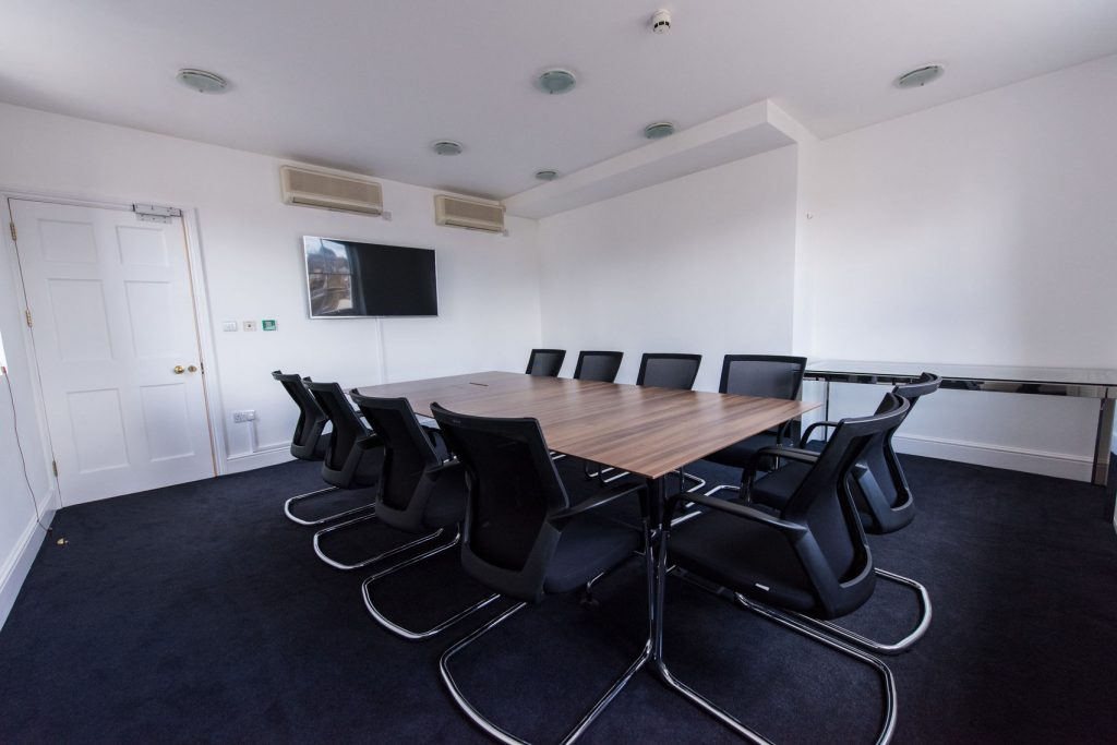 A white meeting room with white walls and blue carpets with a flat screen TV on the back wall.