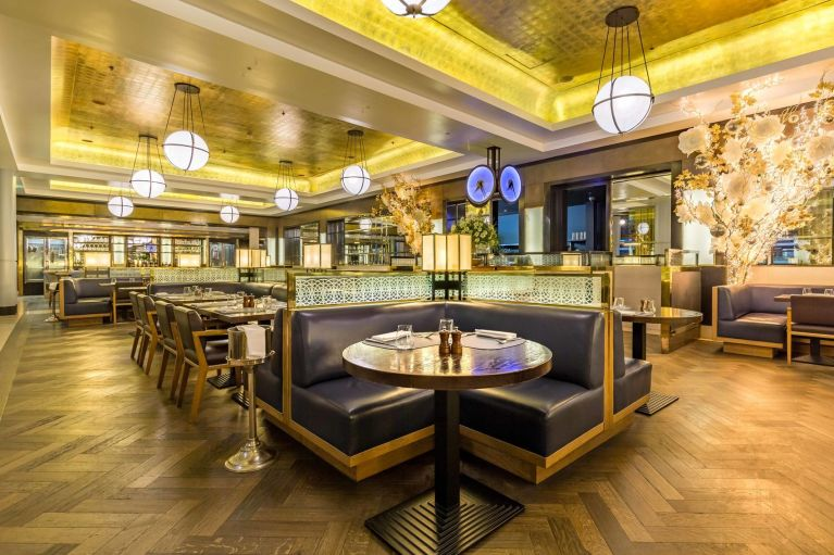 Restaurant space with leather booth seating, round tables and wood panelled flooring