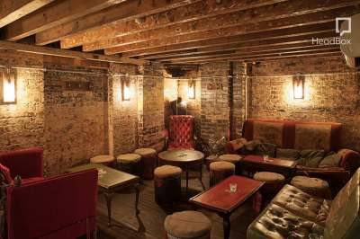 A speakeasy bar with exposed brick walls and a range of seating