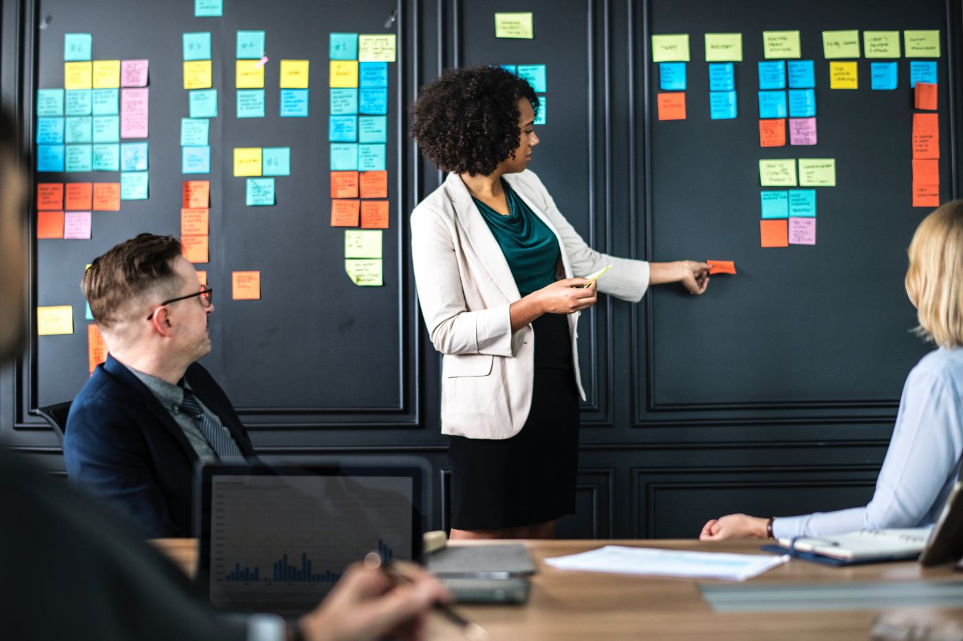 A women sticking post it notes onto a black wall