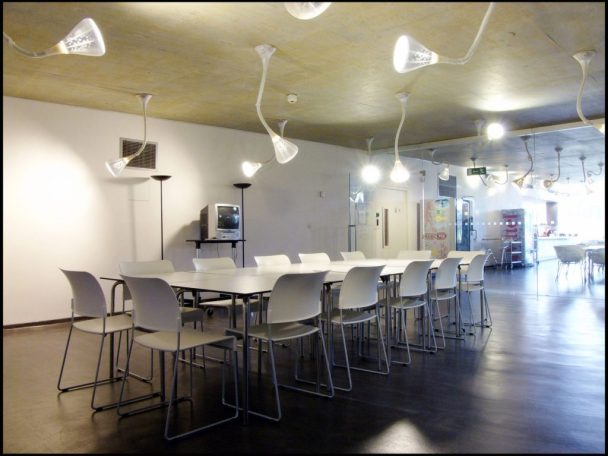 A large meeting room with a boardroom table in the middle surrounded by chairs and their are lights hanging from the ceiling.
