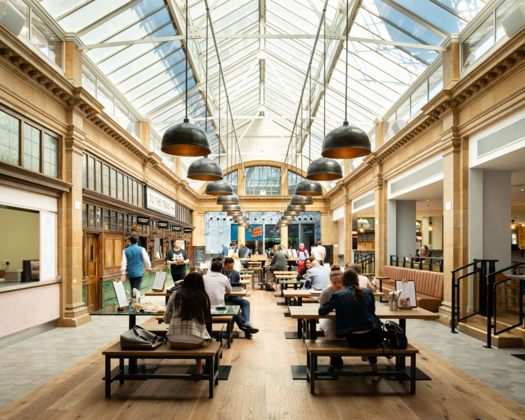 A large indoor street market with high glass ceilings and large copper lights
