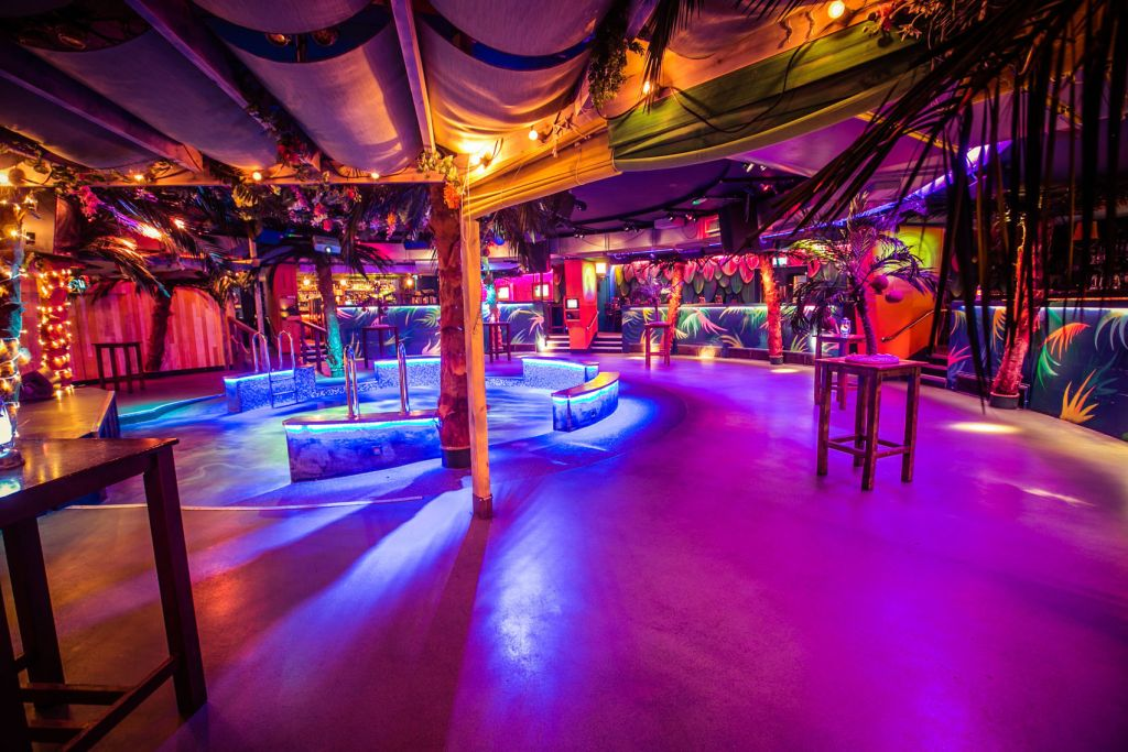 A beach themed club with bright pink lights