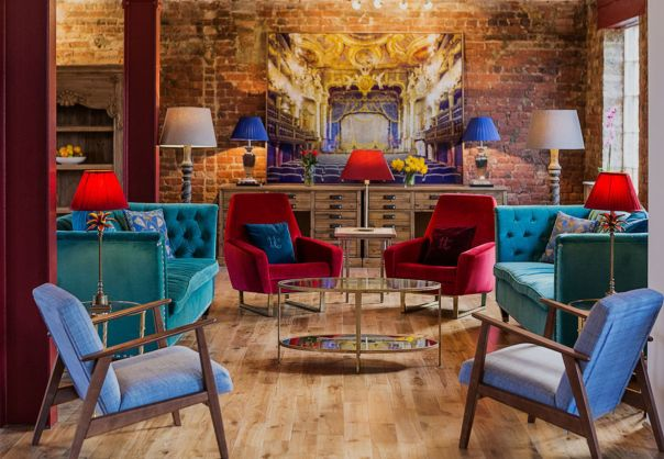 An old warehouse space with a bare brick back wall and blue and red furnishings. A great venue hire option in London