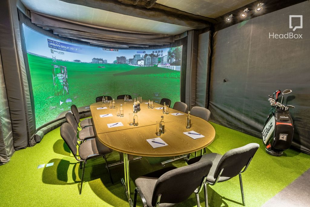 An interactive golf venue. With a large curved screen on the back wall a round meeting room table in the middle and astro turf on the floor.