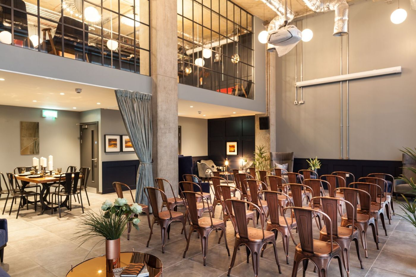 A large event Space with a mezzanine level an rows of chairs