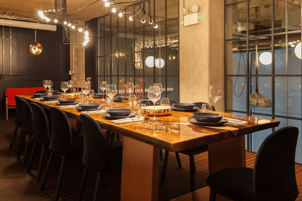 A dark wooden dining table is surrounded by striking chairs. The side wall is glass making it seem bigger. The perfect venue hire London for a private dining event