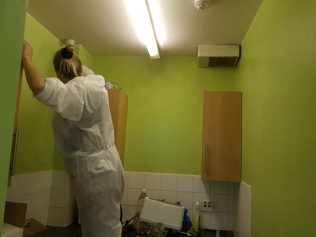 a blonde woman painting kitchen windows green