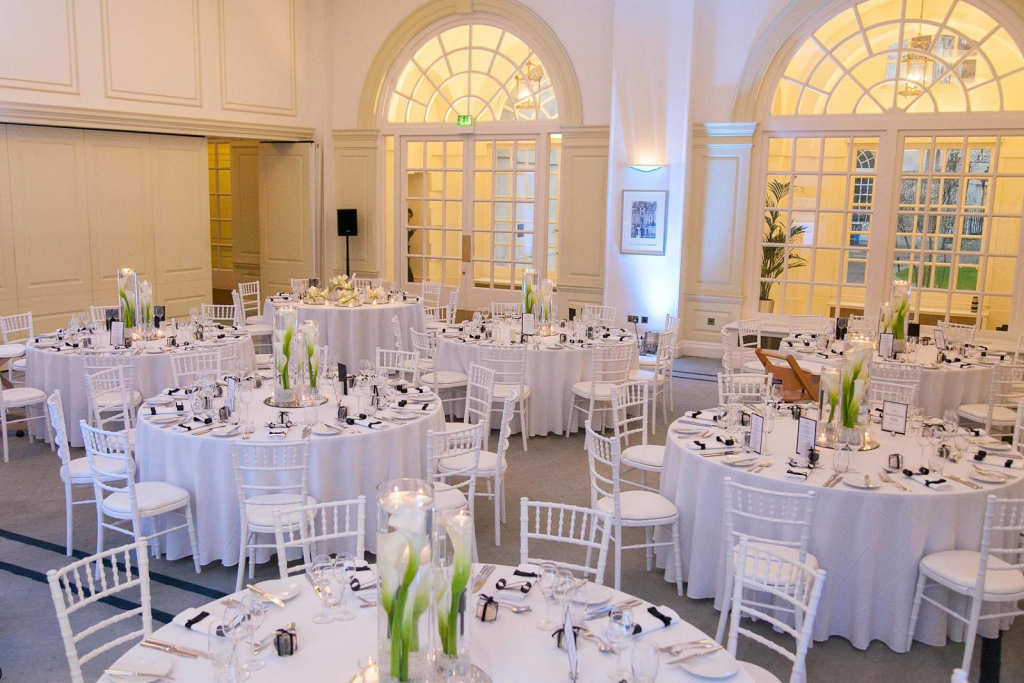 the snow room at BMA House is a large event space painted white with tables and chairs set our for a dining event