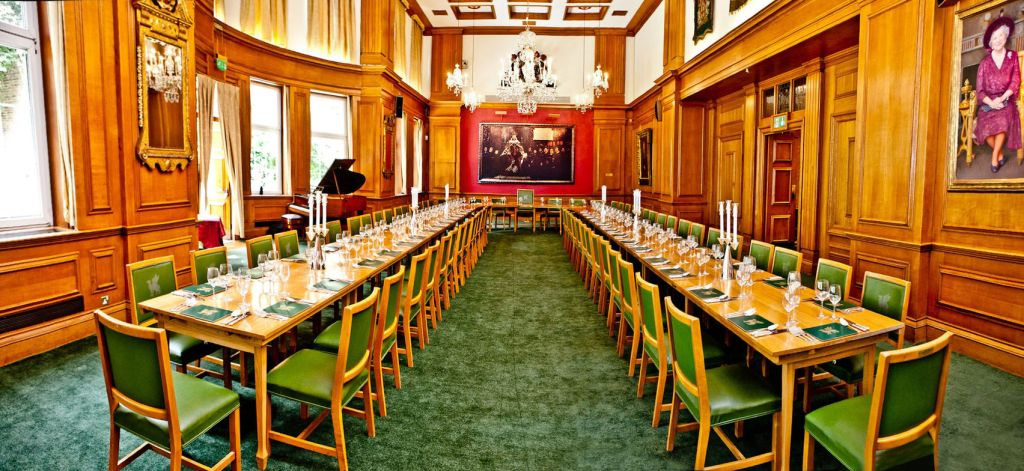 A large hall in London which is set out in boardroom meeting style which a u shaped table. The room has oak orange panelling and green carpets. Oil paintings adorn the walls of this historic hall and a large chandelier in the centre of the room.