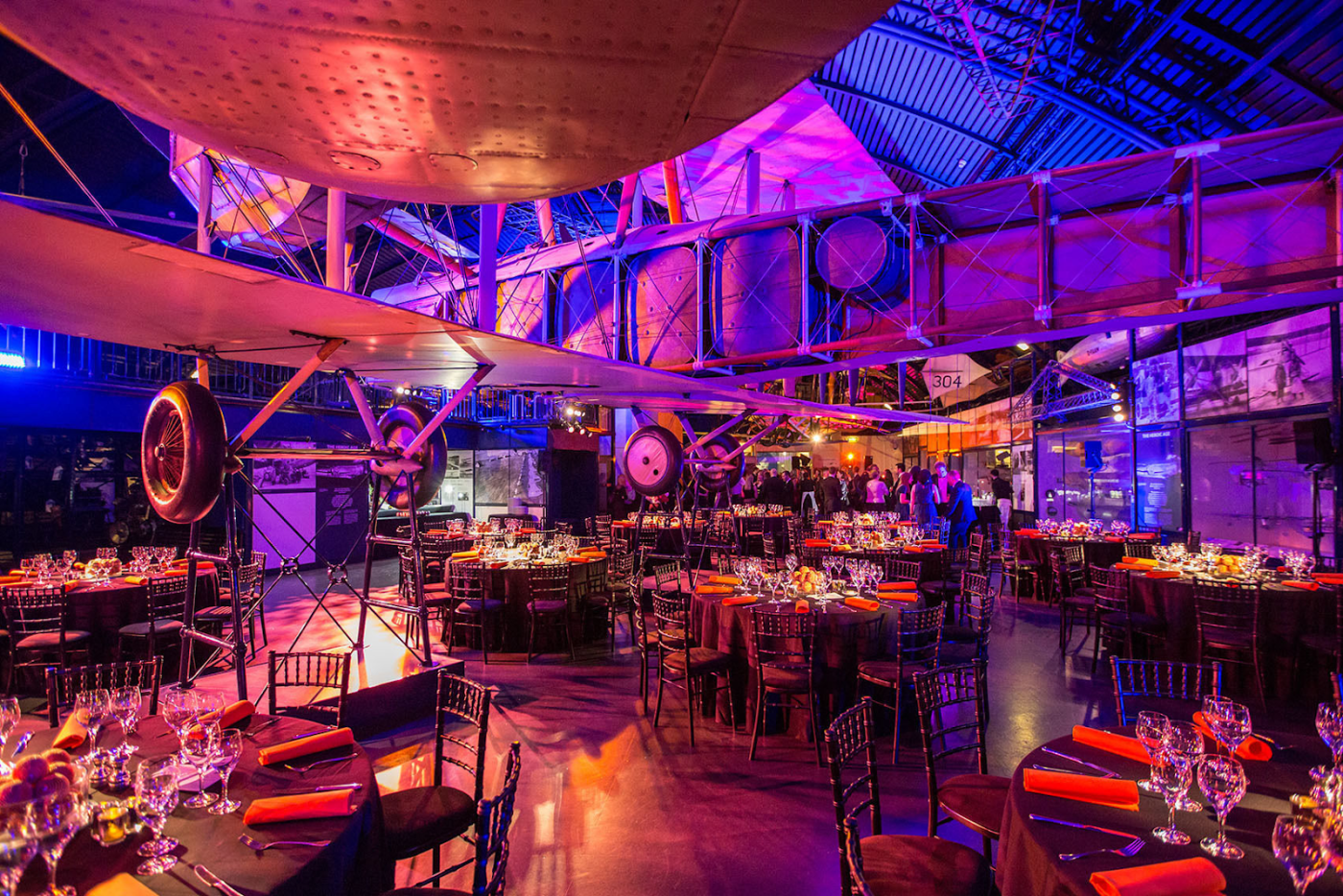 tables and chairs set up for a cabaret style event with a large plane hanging from the ceiling