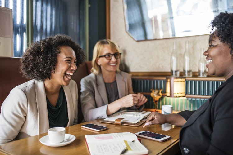 three women sitting around a table chatting and laughing