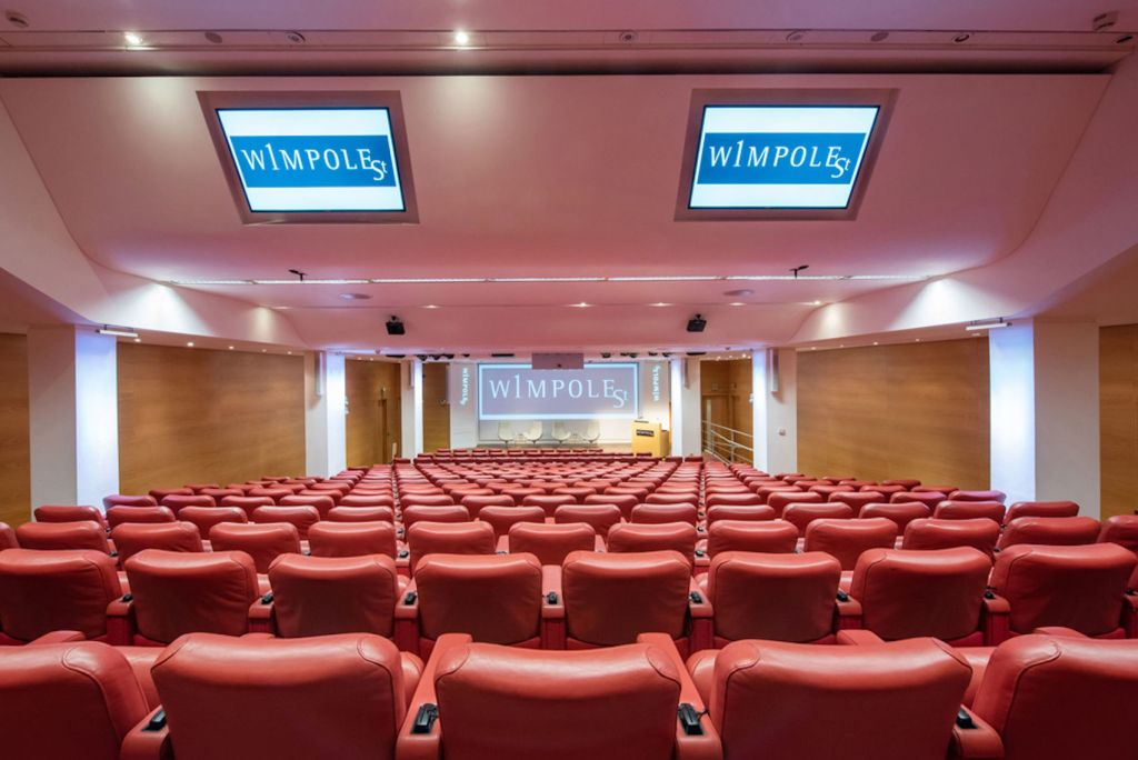 Large conference hall with screens and red seating.
